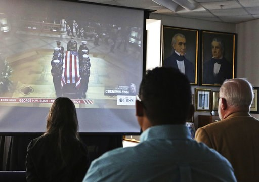 (Jacob Ford/Odessa American via AP). Attendees to George H.W. Bush's funeral viewing at the Presidential Museum and Leadership Library in Odessa, Texas, look on as a military honor guard delivers Bush's casket to the Washington National Cathedral in Wa...