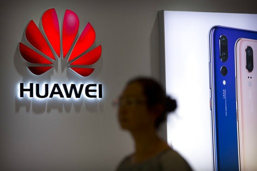 (AP Photo/Mark Schiefelbein, File). FILE - In this July 4, 2018, file photo, a shopper walks past a Huawei store at a shopping mall in Beijing. Canadian authorities said Wednesday, Dec. 5, 2018,  that they have arrested the chief financial officer of C...