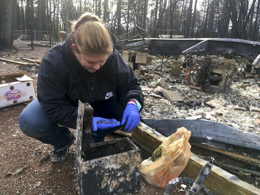 (AP Photo/Don Thompson). In this photo taken Wednesday, Dec. 5, 2018 Jennifer Christensen sorts through items found in a safe at the remains of her home in Paradise, Calif. Christensen and her 2-year-old son, Avery, moved to Paradise about a year ago. ...