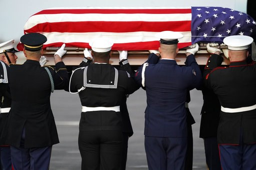 (AP Photo/David J. Phillip, Pool). The flag-draped casket of former President George H.W. Bush is carried by a joint services military honor guard Wednesday, Dec. 5, 2018, at Ellington Field in Houston.