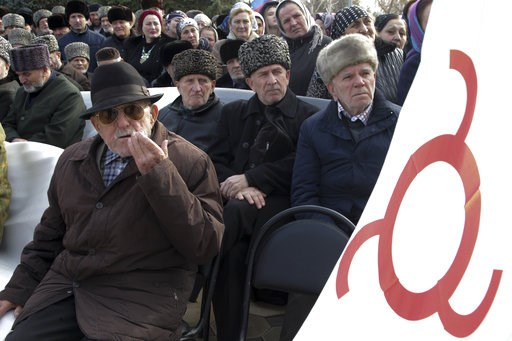 (AP Photo/Musa Sadulayev, File). FILE - In this Tuesday, Nov. 27, 2018 file photo, local people with a Ingushetia region flag attend a protest against the new land swap deal agreed by the heads of the Russian regions of Ingushetia and Chechnya, in Ingu...