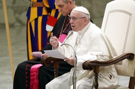(AP Photo/Andrew Medichini). Pope Francis, flanked by Vatican Prefect of the Pontifical Household, Archbishop Georg Ganswein, delivers his message during a weekly general audience, in the Pope Paul VI hall, at the Vatican, Wednesday, Dec. 5, 2018.