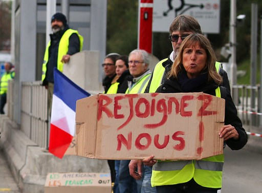 """(AP Photo/Bob Edme). A demonstrator holds a placard reading """" Join us"""" as they stand by toll gates on a motorway at Biarritz southwestern France, Wednesday, Dec.5, 2018. The concessions made by French president Emmanuel Macron's government in a bid to ..."""