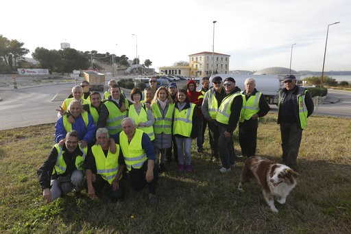 (AP Photo/Claude Paris). A group of demonstrators wearing their yellow vest pose on an occupied traffic circle, Wednesday, Dec. 5, 2018 outside La Mede oil refinery, near Martigues, southeastern France. Trade unions and farmers pledged Wednesday to joi...