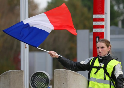 (AP Photo/Bob Edme). A demonstrator holds a french flag at the toll gates on a motorway at Biarritz southwestern France, Wednesday, Dec. 5, 2018.T he concessions made by French president Emmanuel Macron's government in a bid to stop the huge and violen...