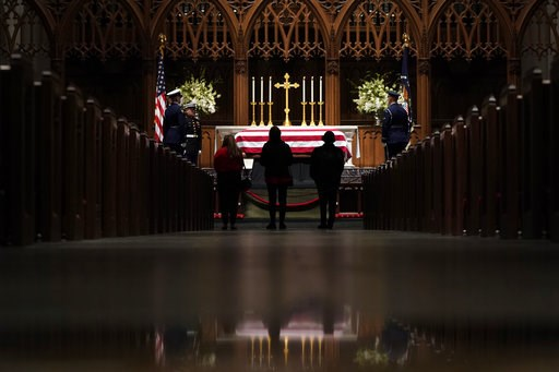 (AP Photo/David J. Phillip, Pool). People pay their respects as former President George H.W. Bush lies in repose at St. Martin's Episcopal Church Wednesday, Dec. 5, 2018, in Houston.