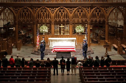 (AP Photo/Mark Humphrey). Visitors pay their respects to the flag-draped casket of former President George H.W. Bush at St. Martin's Episcopal Church, Wednesday, Dec. 5, 2018, in Houston.