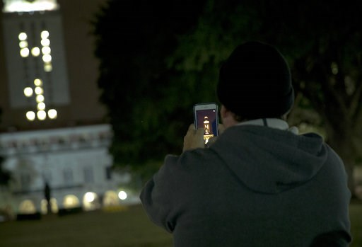 "(Nick Wagner/Austin American-Statesman via AP). A man uses his phone to photograph the University of Texas at Austin tower as it is lit ""41"" in honor of former President George H.W. Bush on Wednesday, Dec. 5, 2018, in Austin, Texas. The nation bid good..."