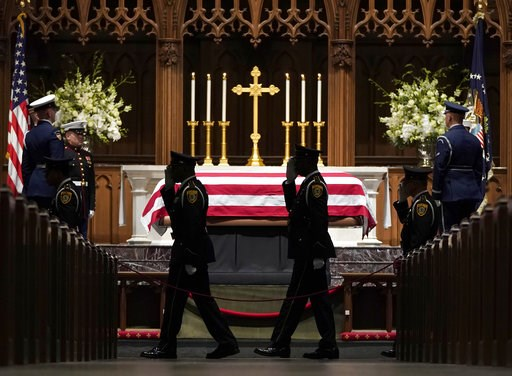 (AP Photo/David J. Phillip, Pool). Military members salute as they pay their respects as former President George H.W. Bush lies in repose at St. Martin's Episcopal Church Wednesday, Dec. 5, 2018, in Houston.