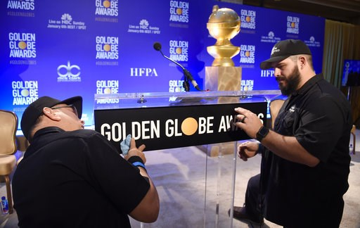 (Photo by Chris Pizzello/Invision/AP). John Langhammer, left, and Brian Cooper, of Crews Unlimited II, set up the podium prior to the announcements of the nominations for the 76th Annual Golden Globe Awards at the Beverly Hilton hotel on Thursday, Dec....