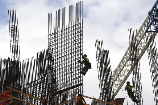 (Amy Beth Bennett/South Florida Sun-Sentinel via AP, File). FILE- In this Sept. 24, 2018, photo metal workers are silhouetted on the top of The Rise, a luxury apartment building under construction in Flagler Village in downtown Fort Lauderdale, Fla. On...