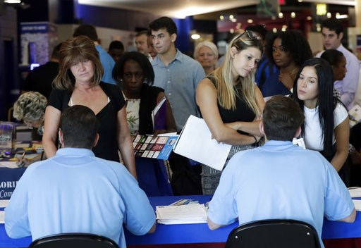 (AP Photo/Lynne Sladky, File). FILE- In this June 21, 2018 file photo, job applicants talks with representatives from Aldi at a job fair hosted by Job News South Florida, in Sunrise, Fla. On Thursday, Dec. 6, payroll processor ADP reports how many jobs...