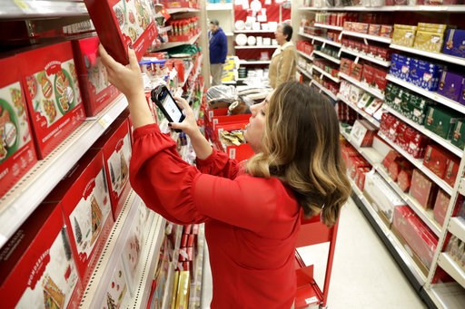(AP Photo/Julio Cortez, File). FILE- In this Nov. 16, 2018, file photo Target employee Lindsay Walker scans an item as she collects merchandise from shelves to prep them for an online order at a Target store in Edison, N.J. On Thursday, Dec. 6, the Ins...