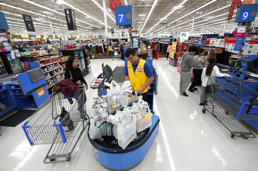 (AP Photo/David J. Phillip, File). FILE- In this Nov. 9, 2018, file photo Walmart associate Luis Gutierrez, center, checks out a customer at a Walmart Supercenter in Houston. On Thursday, Dec. 6, the Institute for Supply Management, a trade group of pu...
