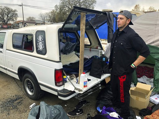 (AP Photo/Jonathan J. Cooper). In this Tuesday, Dec. 4, 2018 photo Michael Jones organizes a pile of donated blankets, sleeping bags and clothes in a fairgrounds parking lot that's become home to some of the people displaced by California's deadliest w...