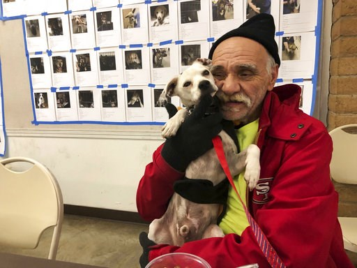 (AP Photo/Jonathan J. Cooper). In this Tuesday, Dec. 4, 2018 photo, Bob Talk cuddles his dog, Princeton, at a Red Cross disaster shelter in Chico, Calif. Talk had lived in his trailer for three days when fire swept through the town of Paradise and dest...