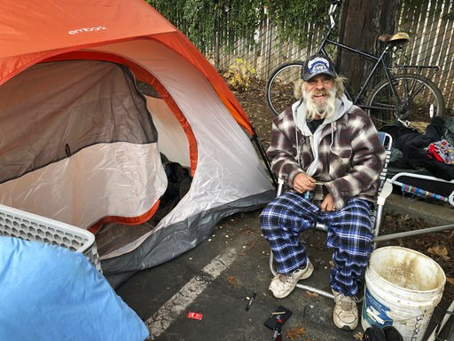 (AP Photo/Jonathan J. Cooper). In this Tuesday, Dec. 4, 2018 photo, Steve Wilson poses for a photo next to the tent where he's been sleeping in the parking lot of an abandoned Toys R Us in Chico, Calif. Wilson, who was homeless in Chico before the wors...