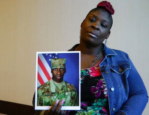 """(AP Photo/Jay Reeves, File). FILE - In this Nov. 27, 2018, file frame from video, April Pipkins holds a photograph of her deceased son, Emantic """"EJ"""" Bradford Jr., during an interview in Birmingham, Ala. Bradford, who was licensed to carry a gun, was ki..."""