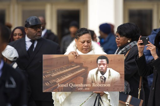 (Tyler LaRiviere/Chicago Sun-Times via AP, File). FILE - In this Nov. 8, 2018, file photo, a woman holds up a sign with Jemel Roberson's image at his funeral in Chicago. Roberson, who was working security at a bar, was killed on Nov. 11 while holding a...