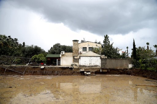 (AP Photo/Petros Karadjias). A house is seen by flooded area after heavy rain overnight near Kerynia city in the Turkish Cypriots breakaway north part of Cyprus, Thursday, Dec. 6, 2018. Police in the breakaway north of ethnically split Cyprus say the b...