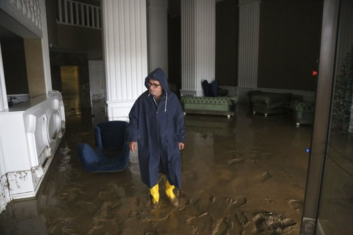 (AP Photo/Petros Karadjias). A man walks inside the reception of a flooded hotel after heavy rain fell overnight near Kerynia city in the Turkish Cypriots breakaway north part of Cyprus, Thursday, Dec. 6, 2018. Police in the breakaway north of ethnical...