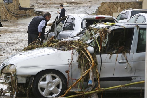(AP Photo/Petros Karadjias). A man looks a flooded cars outside of a flooded hotel after heavy rain over night near Kerynia city in the Turkish Cypriots breakaway north part of Cyprus, Thursday, Dec. 6, 2018. Police in the breakaway north of ethnically...