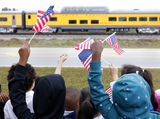 (AP Photo/Michael Wyke). Students from Salyer Elementary School wave flags as the train carrying the body of former president George H.W. Bush travels past their school on the way to Bush's final internment Thursday, Dec. 6, 2018, in Spring, Texas.