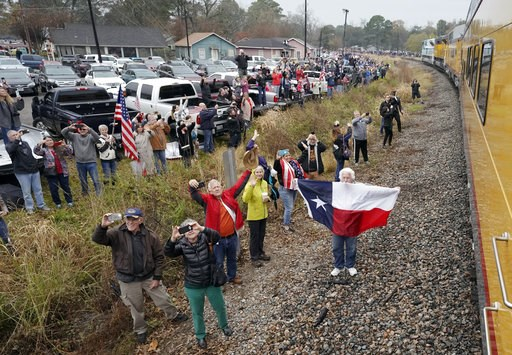 (AP Photo/David J. Phillip, Pool). People pay their respects as the train carrying the casket of former President George H.W. Bush passes Thursday, Dec. 6, 2018, along the route from Spring to College Station, Texas.