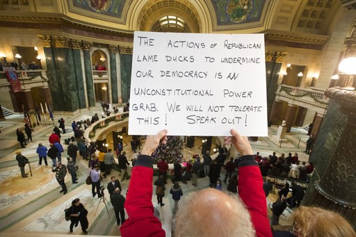 (Mark Hoffman/Milwaukee Journal-Sentinel via AP, File). FILE - In this Tuesday, Dec. 4, 2018 file photo, people protest the legislature's extraordinary session during the official Christmas tree lighting ceremony at the Capitol in Madison, Wis. Demonst...