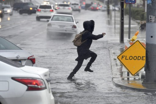 (James Quigg/The Daily Press via AP). A pedestrian leaps across a flooded portion of the La Paz and Seventh Street intersection as a winter storm arrived, Thursday, Dec. 6, 2018 in Victorville, Calif. The second round of a fall storm dumped snow and ra...