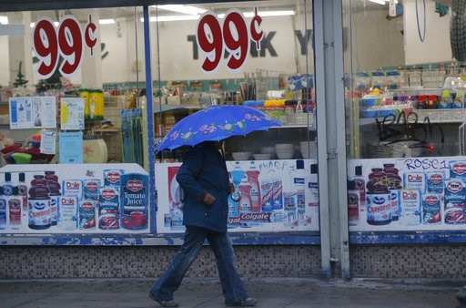 (AP Photo/Damian Dovarganes). A pedestrian walks past a 99-Cents store under light rain in Los Angeles Wednesday, Dec. 5, 2018. A fall storm is causing slick conditions on Southern California freeways but isn't expected to generate enough rain to trigg...