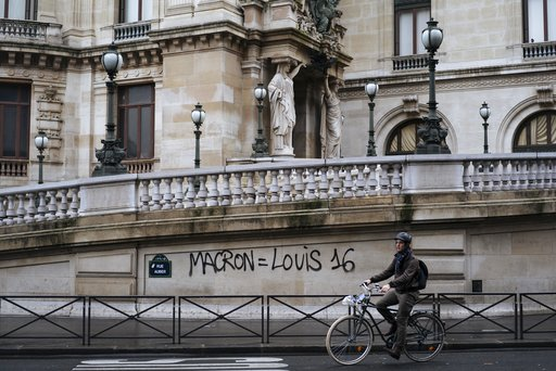 "(AP Photo/Kamil Zihnioglu, File). FILE - In this Dec. 2, 20118 file photo, a man rides his bicycle past by a graffiti on the Paris Garnier Opera house in Paris that reads: ""Macron is equal to Louis 16"", referring to the King of France during the French..."