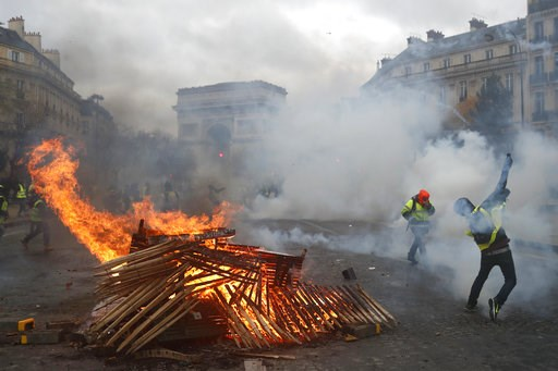 (AP Photo/Thibault Camus, File). FILE - In this Dec. 1, 2018 file photo, demonstrators throw items near a burning barricade near the Arc de Triomphe during a demonstration. There are parallels for unpopular French President Emmanuel Macron in the demis...