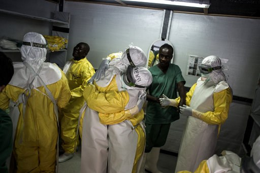 (John Wessels/Medecins Sans Frontieres via AP). In this photo taken Wednesday, Nov. 7, 2018 and made available Tuesday, Dec. 4, 2018, health workers embrace whilst putting on their personal protective equipment before heading into the red zone of a Med...