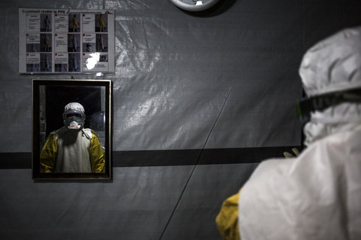(John Wessels/Medecins Sans Frontieres via AP). In this photo taken Saturday, Nov. 3, 2018 and made available Tuesday, Dec. 4, 2018, a health worker is seen wearing his personal protective equipment before entering the red zone of a Medecins Sans Front...