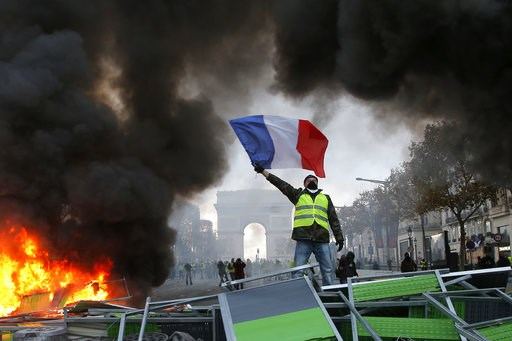 (AP Photo/Michel Euler, File). FILE - In this Nov. 24, 2018 file photo, a demonstrator waves the French flag on a burning barricade on the Champs-Elysees avenue with the Arc de Triomphe in background, during a demonstration against the rise of fuel tax...