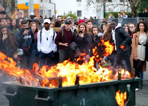 (AP Photo/Bob Edme). Students watch a burning trash bin outside their school in Bayonne, southwestern France, Thursday, Dec.6, 2018. Protesting students are disrupting schools and universities Thursday, and drivers are still blocking roads around Franc...