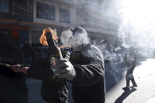 (AP Photo/Giannis Papanikos). A hooded youth prepares to throw a petrol bomb at riot police in the northern Greek city of Thessaloniki, on Thursday, Dec. 6, 2018 during a rally commemorating the killing of a 15-year old student back in 2008. School and...