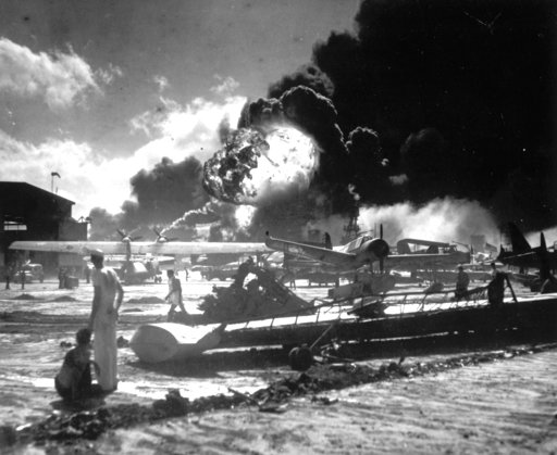 (U.S. Navy via AP, File). In this Dec. 7, 1941 file photo, sailors stand among wrecked airplanes at Ford Island Naval Air Station as they watch the explosion of the USS Shaw in the background, during the Japanese attack on Pearl Harbor, Hawaii. About 2...