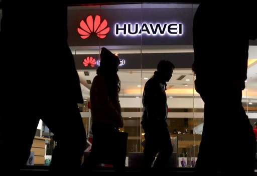 (AP Photo/Ng Han Guan). Pedestrians walk past a Huawei retail shop in Beijing Thursday, Dec. 6, 2018. China on Thursday demanded Canada release a Huawei Technologies executive who was arrested in a case that adds to technology tensions with Washington ...