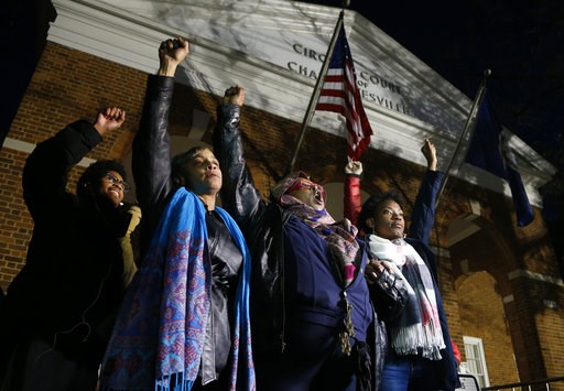 (AP Photo/Steve Helber). Local activists raise their fists outside Charlottesville General District Court after a guilty verdict was reached in the trial of James Alex Fields Jr., in Charlottesville, Va., Friday, Dec. 7, 2018. Fields was convicted of f...