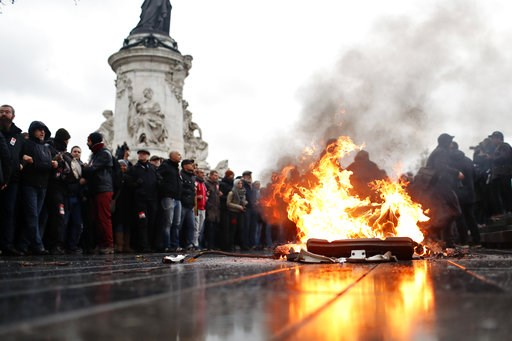 (AP Photo/Thibault Camus). A bin is burning as school children demonstrate in Paris, Friday Dec.7, 2018. Footage showing the brutal arrest of high school students protesting outside Paris is causing a stir ahead of further anti-government protests this...