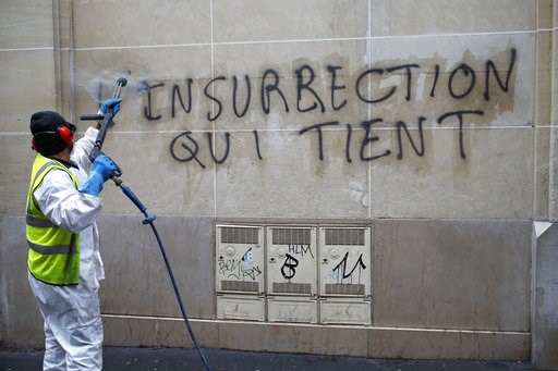 """(AP Photo/Francois Mori). A worker cleans a graffiti reading """"long term unrest"""" near the Champs-Elysees avenue, Friday, Dec. 7, 2018 in Paris. France was mobilizing tens of thousands of police officers and closing landmarks including the Eiffel Tower a..."""