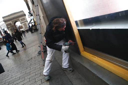 (AP Photo/Francois Mori). A worker screws a wooden plank to protect a shop windows on the Champs-Elysees avenue, Friday, Dec. 7, 2018 in Paris. Many shop owners across the French capital are getting ready for the violence, setting up walls with carton ...