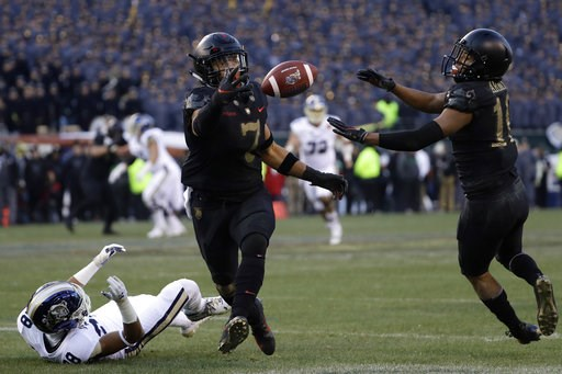 (AP Photo/Matt Slocum). Army's Jaylon McClinton, center, intercepts a pass tipped by teammate Mike Reynolds, right, that was intended for Navy's Mychal Cooper during the first half of an NCAA college football game, Saturday, Dec. 8, 2018, in Philadelph...