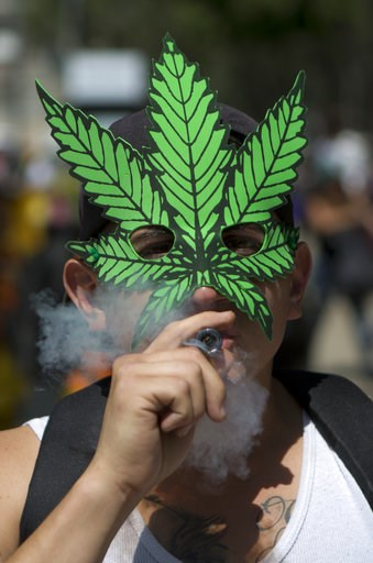 (AP Photo/Eduardo Verdugo, File). FILE - In this April 20, 2018, file photo, a young man smokes marijuana to celebrate the International Day for Cannabis in Mexico City. California became America's largest legal marketplace in 2018, while Canada became...