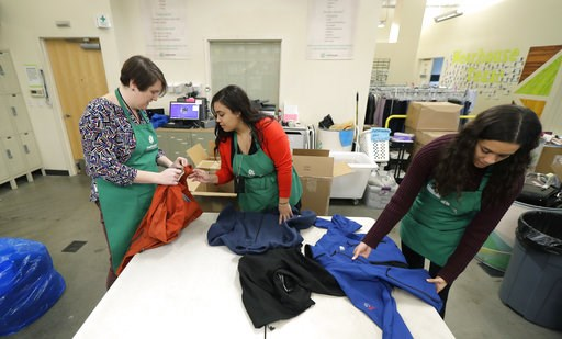 (AP Photo/Ted S. Warren). In this Friday, Dec. 21, 2018, photo, from left, Rebecca Schaechter, Nicole Herron and Rachel Herron fold and sort donated clothes at Treehouse, a nonprofit organization in Seattle that serves the needs of children in the fost...
