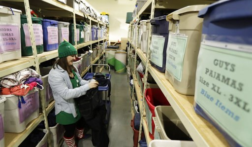 (AP Photo/Ted S. Warren). In this Friday, Dec. 21, 2018, photo, Maddi Heim folds and sorts donated clothes at Treehouse, a nonprofit organization in Seattle that serves the needs of children in the foster-care system. The charity was one of several tha...