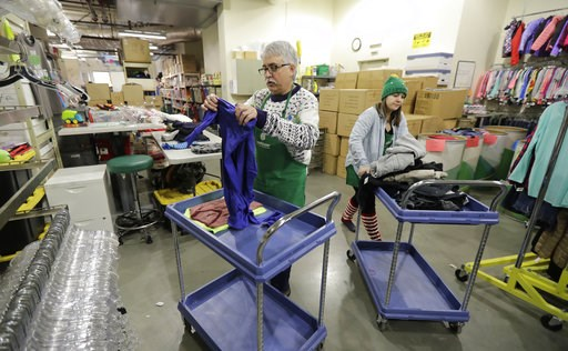 (AP Photo/Ted S. Warren). In this Friday, Dec. 21, 2018, photo, Chris Meyer, left, and Maddi Heim, fold and sort donated clothes at Treehouse, a nonprofit organization in Seattle that serves the needs of children in the foster-care system. The charity ...