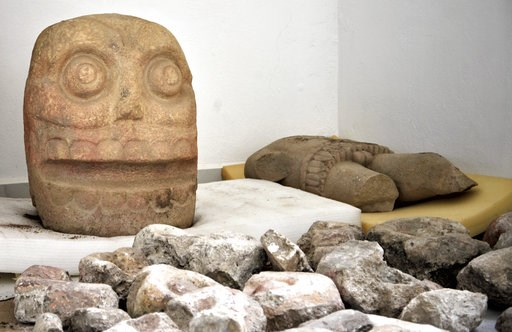 (Meliton Tapia Davila/INAH via AP). In this 2018 photo provided by Mexico's National Institute of Anthropology and History, INAH, a skull-like stone carving and a stone trunk depicting the Flayed Lord, a pre-Hispanic fertility god depicted as a skinned...